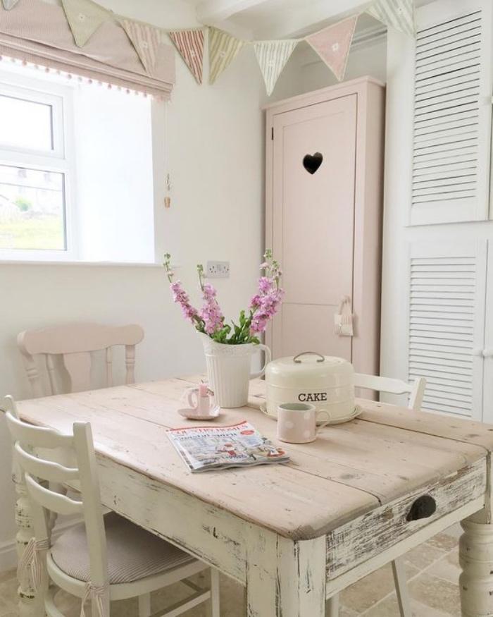 shabby chic decoration dans la cuisine, table en bois massif patiné, chaises en bois, armoire rose, meuble de rangement blanc, carreaux en pierre, guirlande de fanions
