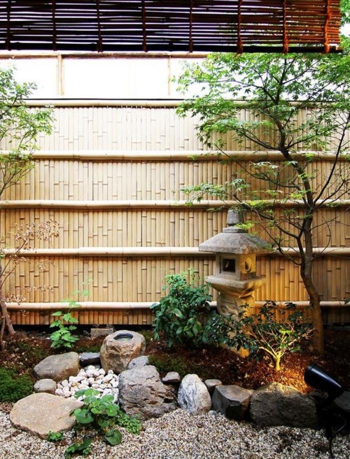 gravier, pierres et lanterne en pierre, arbres et arbustes bas, cloison mur en bambou, idée de coin repos