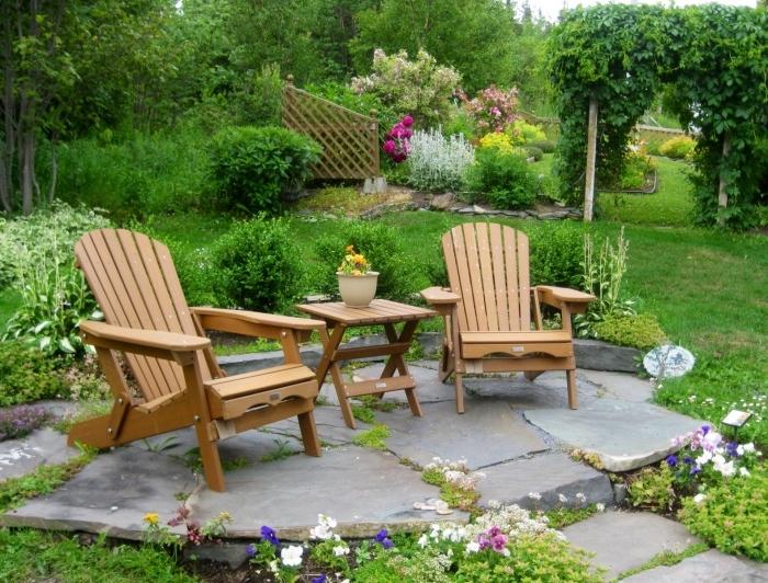 jardin zen, pelouse et fleurs, un terrain en pierres, coin repos, table et chaise longue en bois, vegetation florissante