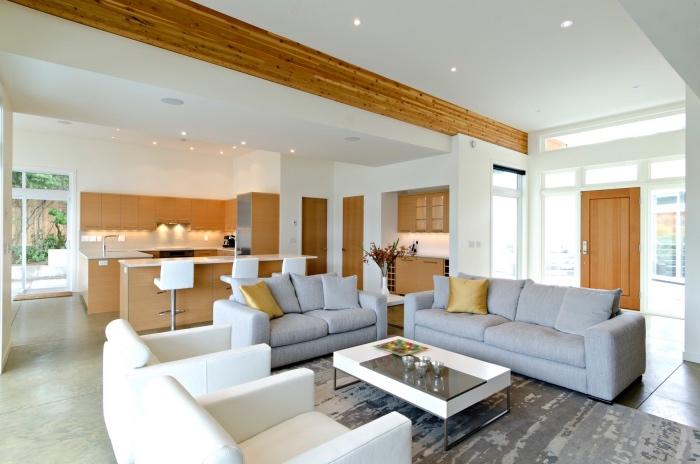 petite cuisine équipée en bois avec bar et ouverture sur un salon avec canapés gris et fauteuils blancs, table basse noir et blanc, tapis gris, poutre apparente