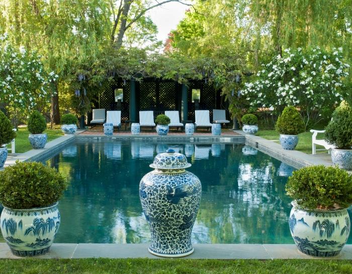 idee amenagement jardin avec une grande piscine, entourée de gazon, vases style bord de mer, avec des buis dedans, plusieurs chaises longues, brise-bue