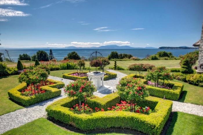 idee amenagement jardin, buis et plusieurs rosier sur un gazon vert, un arc blanc, vue sur la mer