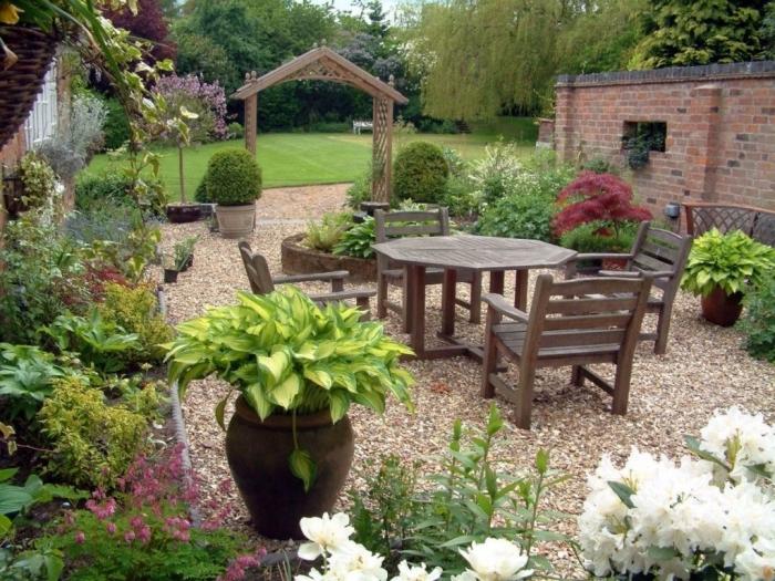 decoration zen, sol recouvert de gravier, une bordure de plantes, petite salle à manger en plein air avec une table et chaises en bois