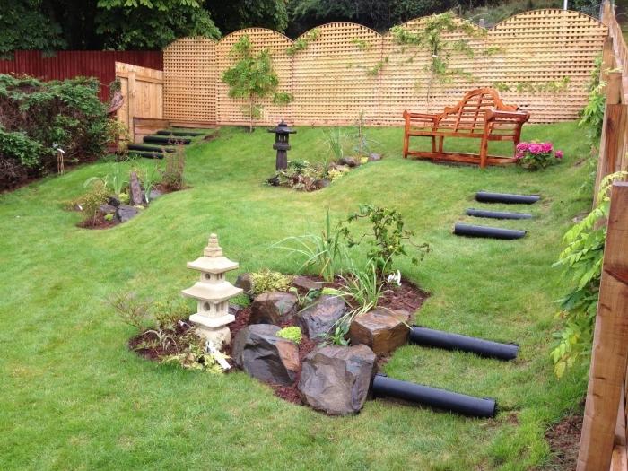 decoration zen jardin en pente, pierres, lanterne, banc en bois, cloture en bois, idée amenagement extérieur végétalise