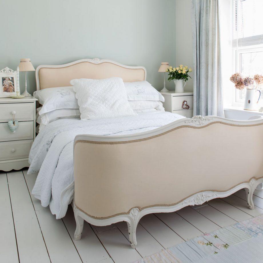 shabby chic lit beige, linge de lit blanc, tables de nuit blanches, parquet blanchi, mur couleur vert pastel clair, bouquets de fleurs