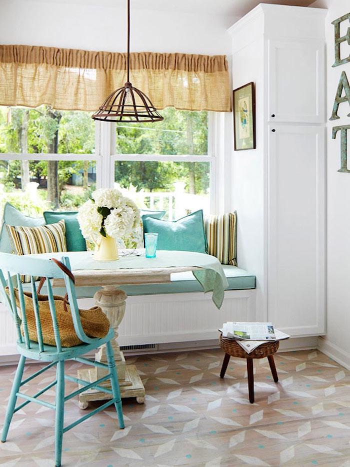 canapé shabby chic près de la fenêtre, table en bois vintage usée, chaise bleu pastel vintage, bouquet de fleurs blanches, suspension en metal design