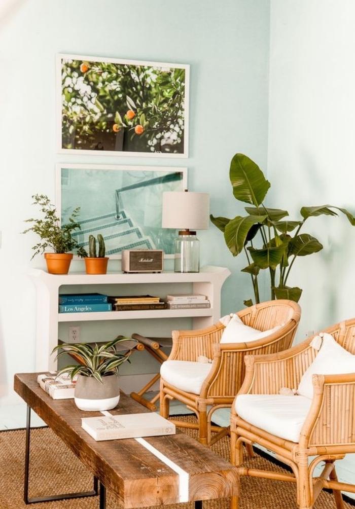 idée de salon vert d eau, table basse en planche de bois et pieds en metal, chaises en bois avec coussins de chaise blancs, étagère rangement blanche, cadres decoratifs, photographies fraiches