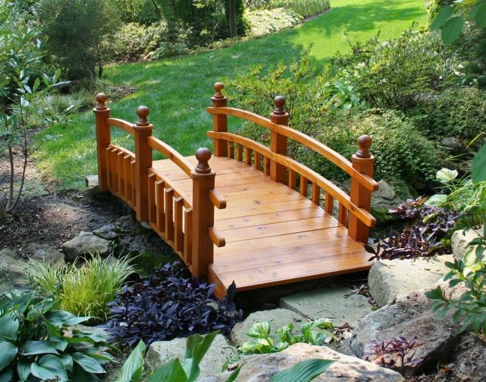 element essentiel du jardin zen, petit pont en bois, arbustes, pelouse et pierres, vegetation verte