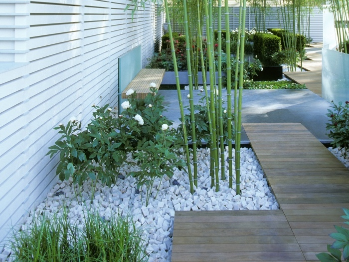 decoration zen dans un jardin moderne, dalles en pierres et pierres deco, fleurs, buis, bambou et cloture en bois