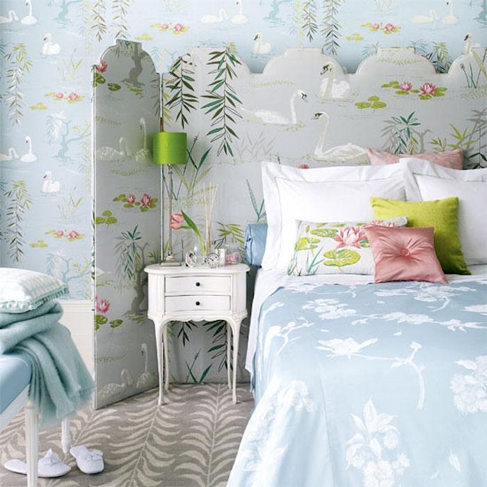 chambre shabby chic, papier peint bleu pastel, motif étang avec nenuphares, couverture de lit bleu, coussins multicolores, parquet gris, table de nuit baroque
