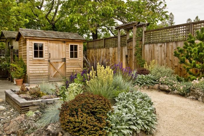 aménager son jardin idée, sol en gravier avec des parterres de fleurs et de pierres, une sorte de rockaille fleurie, cabane de jardin en bois