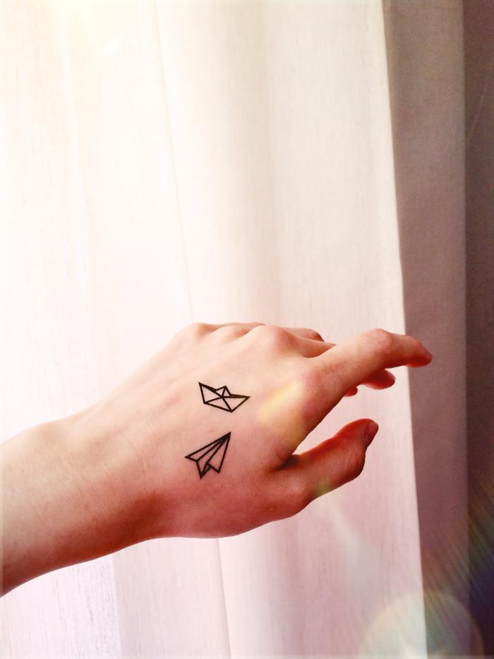 idée originale pour un tatouage minimaliste délicat et féminin sur la main, de petits bateau et avion en papier inspirés de l'art d'origami