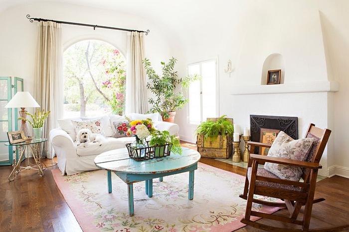 salon shabby chic blanc avec cheminée tapis rose a motifs floraux, chaise à bascule, table basse bleue usée, canapé blanc et coussins fleuris, deco de plantes