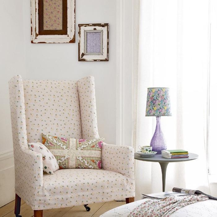 idée shabby chic, fauteuil blanc a motifs floraux, parquet en bois, deco murale de cadres, table d appoint grise lampe shabby chic