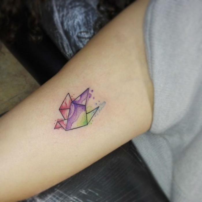 une petite grue aquarelle tatouée au bras, idée pour un tatouage minimaliste doux et féminin