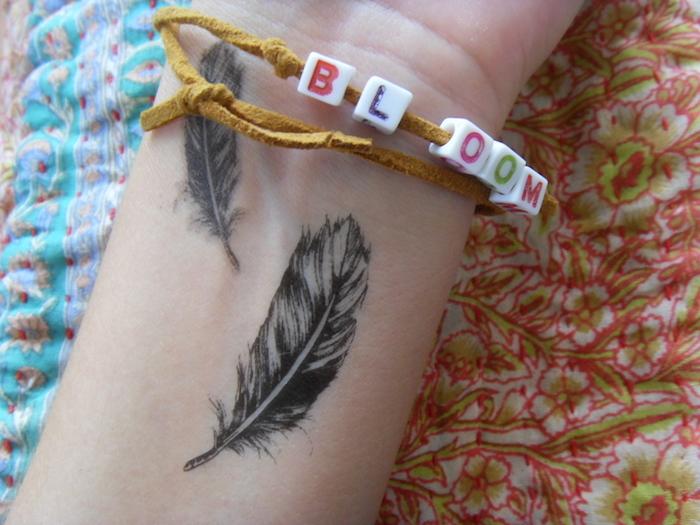 tatouage femme, bracelet avec lettres pour femme, tatouage sur le poignet à petites plumes
