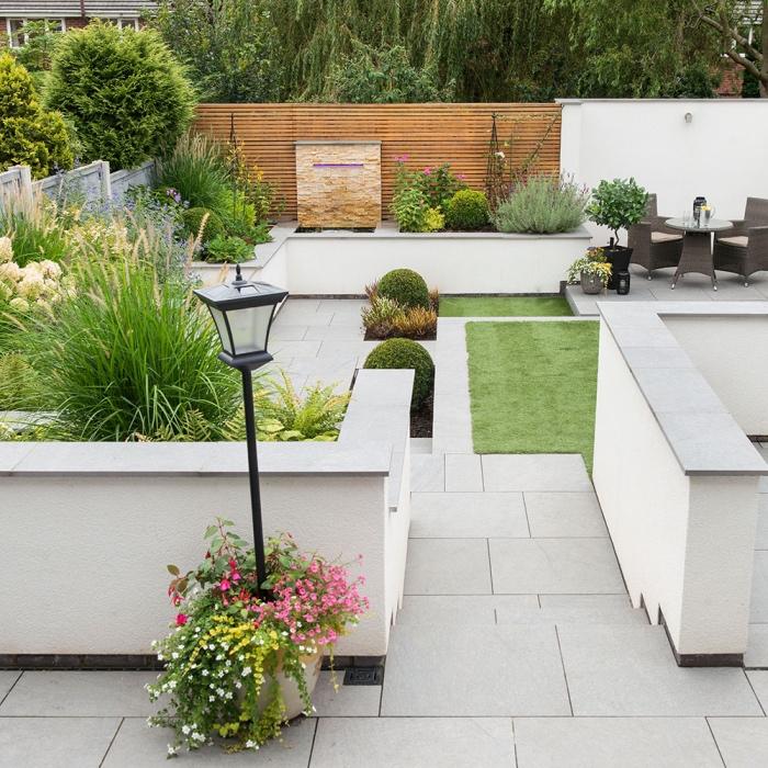 idee deco jardin, revêtement en dalles de béton, salon de jardin en rotin, espaces verts avec des gazons, arbustes et arbres le long d une clôture en bois