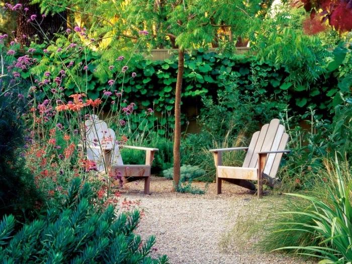 idee amenagement jardin, chemin de gravier, chaise longues en bois, arbre, arbustes, plantes grimpantes