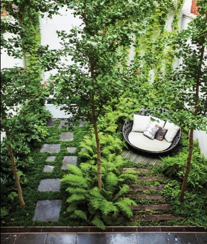 exemple amenagement jardin, canapé rond design sur un lit en bambou, chemin de dalles de pierre, arbustes, arbres