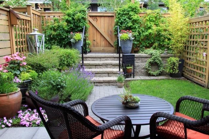 modele amenagement petit jardin, salon de jardin, table et chaises tressées, petit gazon, parterre de fleurs et arbustes, palissade et separation ajrdin en bois
