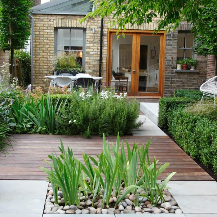 idee amenagement jardin, une terrasse surélevée en dalles de béton et bois de teck, plusieurs buis, arbres et arbustes, coin repas avec table en chaises