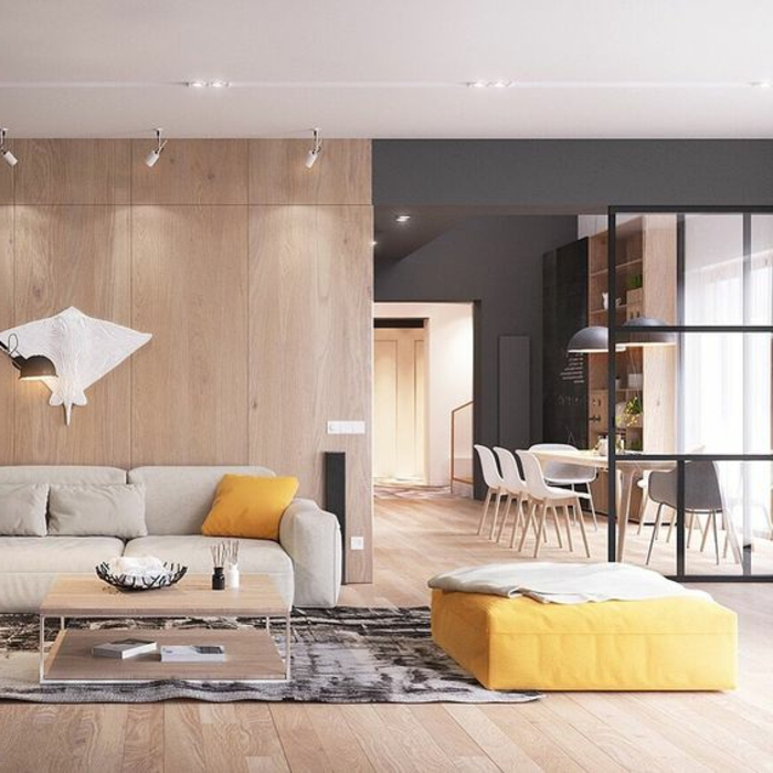 idee de deco salon, lambris mural en bois, pouf jaune, sofa contemporain, salle de déjeuner