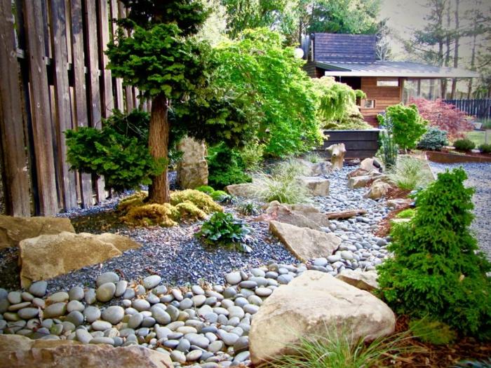 jardin zen japonais avec une riviere en galets, entourée de grosses pierres, arbres et arbustes verts, clôture en bois, maison dans les bois, chalet design