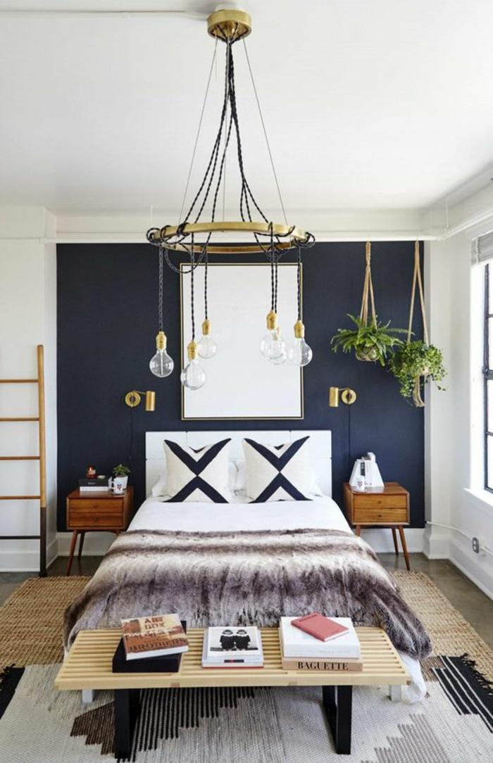 chambre complete adulte avec des grands coussins aux formes graphiques et grand luminaire massif style porte bougies avec des grandes ampoules