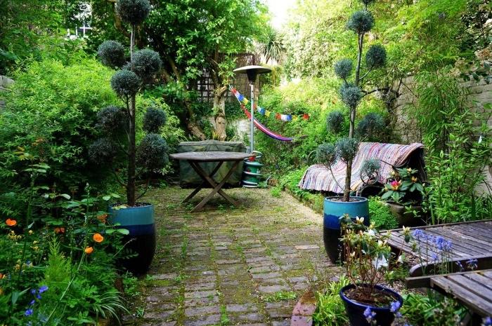 comment paysager son jardin, un espace détente en dalles de pierre, un banc et une table de jardin, petits arbres et arbustes autour