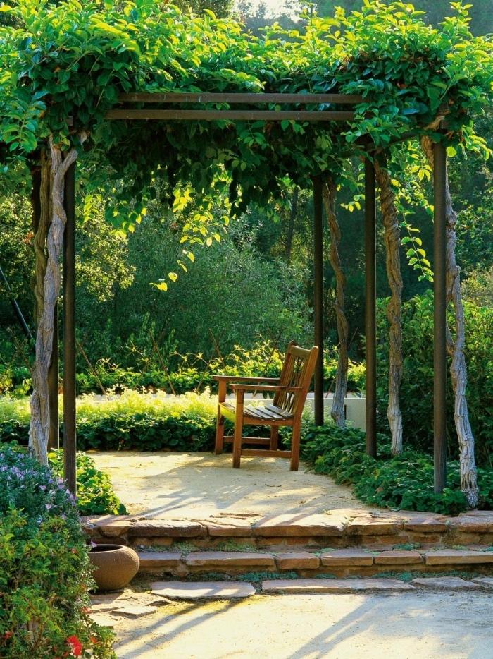 idee jardin deco, un petit banc en bois sous une tonnelle de jardin végétalisé, jardin avec plusieurs fleurs, arbres et buis