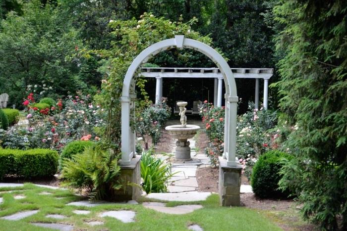 amenagement jardin avec un arc, pergola ancienne, chemin de dalles de béton, entouré de rosiers, buis, arbustes et arbres, cadre forestier