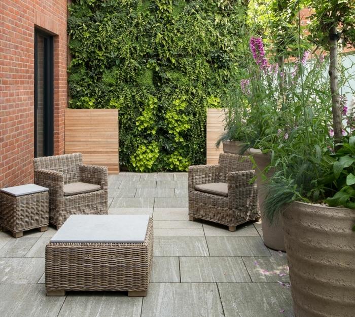 idée de génie jardin, patio salon de jardin en dalles de pierre, fauteuils et tables en rotin, mur végétal et gros pots de fleurs