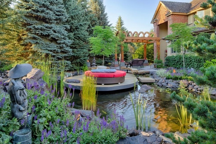 comment aménager son jardin zen, un étang, bassin aquatique, entouré de pierres, rochers, plusieurs arbres, statue japonaise, ilot de détente avec canapé et salon de jardin au fond