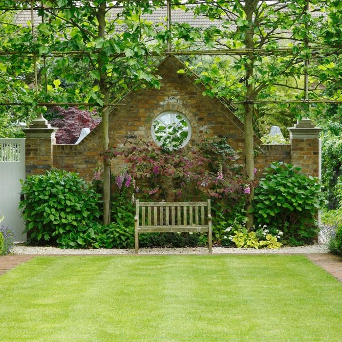 amenagement jardin exterieur, un gazon vert avec une bordure d arbustes et des fleurs, arbres, clôture en briques, cadre nature campagne