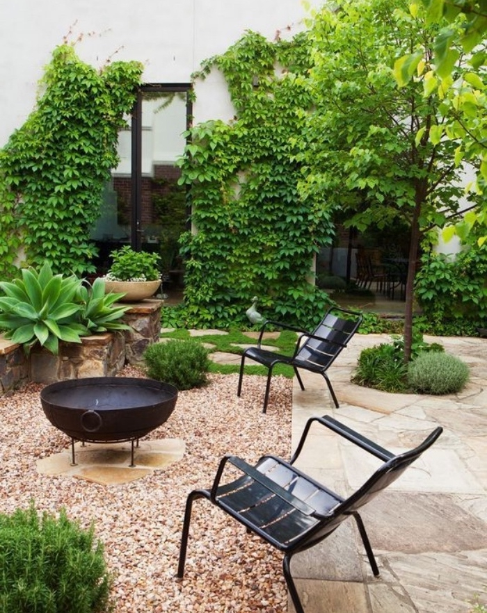 aménager son jardin, un espace barbecue avec des chaises noires en metal, mur envahi de lierre, plante grimpante, maison de campagne, dalles de pierre