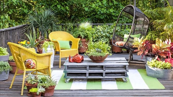 aménager son jardin sur une terrasse, une table en palette à roulettes, chaises tressées jaunes, revêtement en teck, balançoire suspendue en bois, plusieurs plantes dans des pots de fleurs