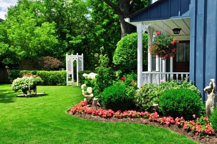 idee jardin a créer soi même avec une gazon, brouette avec des fleurs plantées dedans, une parterre de fleurs et d arbustes, un arc blanc