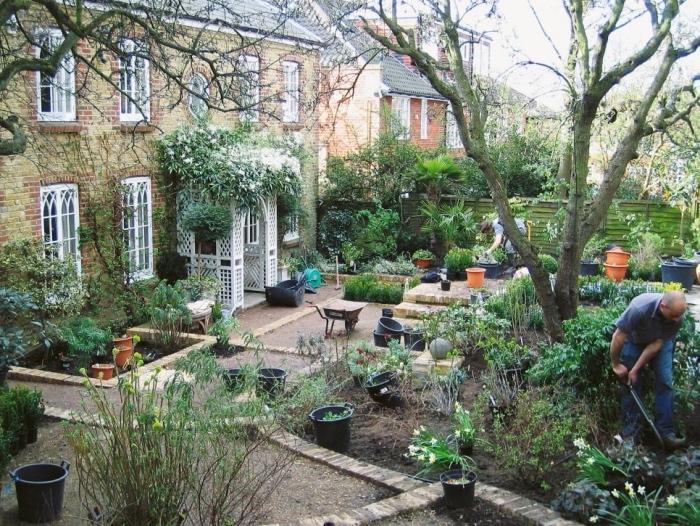 aménager son jardin, maison style cottage anglais, un jardin avec plusieurs carrés végétalisés à différente hauteur, entrée en arc fleuri, arbres et fleurs