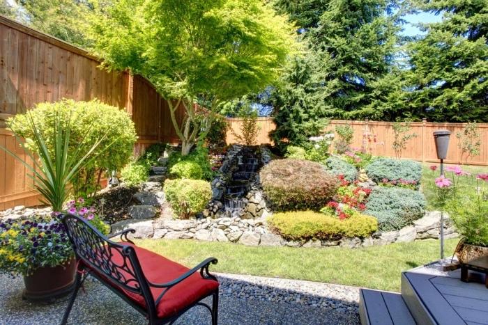 idee deco jardin avec gazon, cascade d eau dans une rockaille fleurie, d arbustes et d arbres, un banc en metal avec coussin d assise rouge