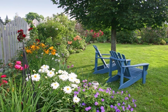 idee jardin amenagement simple et esthétique gazon avec une parterre de fleurs le long d une palissade, arbre et chaise longues bleues à l ombre