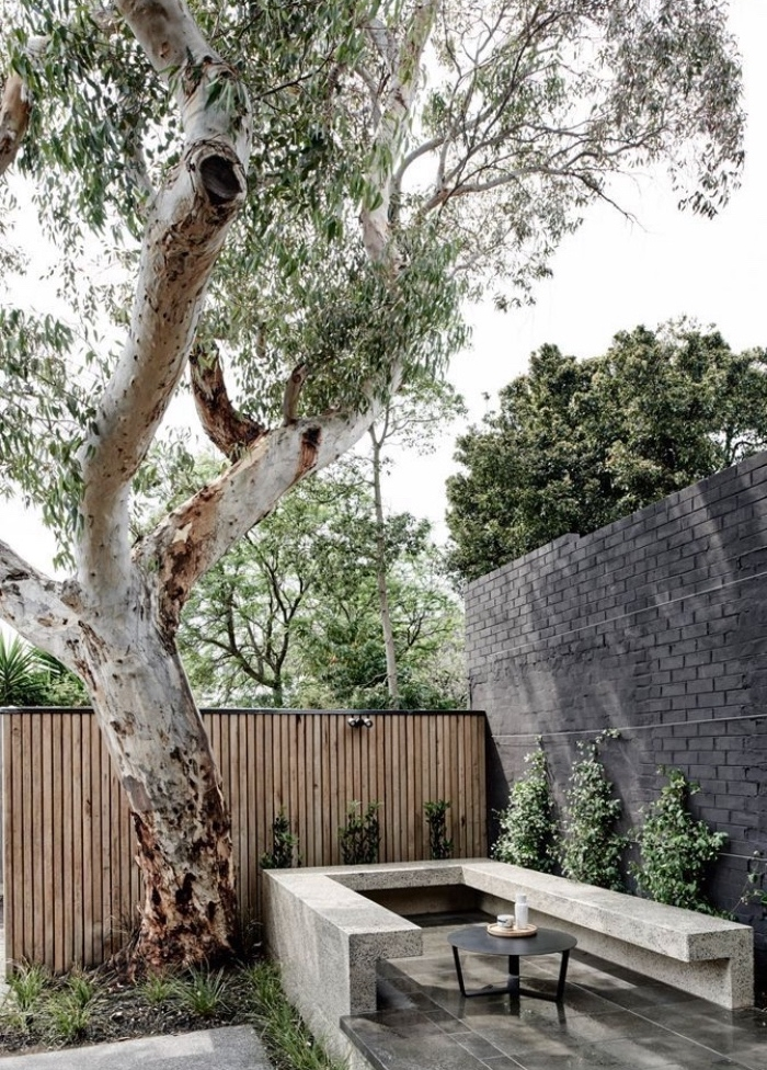 idee amenagement jardin sec, espace détente, banc en béton et petit table basse metallique noire, arbre à couronne verte, clôture en bois, arbustes