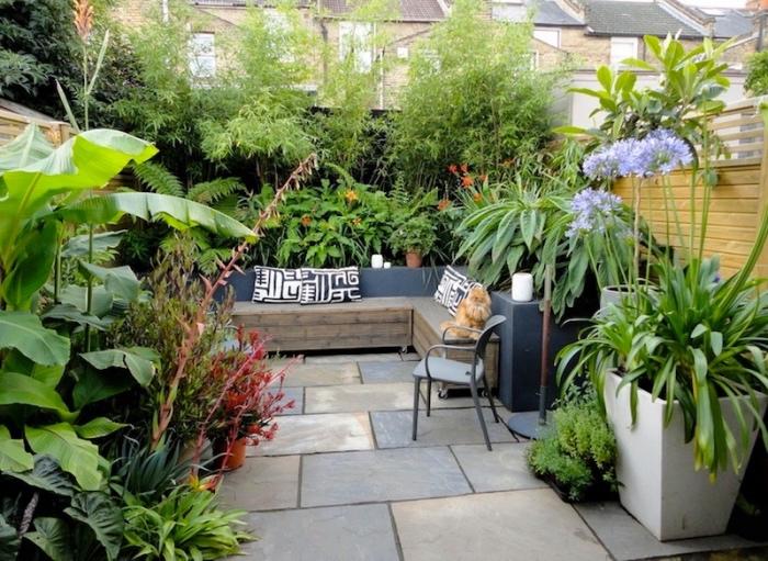 amenagement petit jardin, revêtement en dalles de pierre, canapé en bois avec des coussins noir et blanc, plusieurs plantes dans des pots de fleurs autour d une clôture en bois, bambou