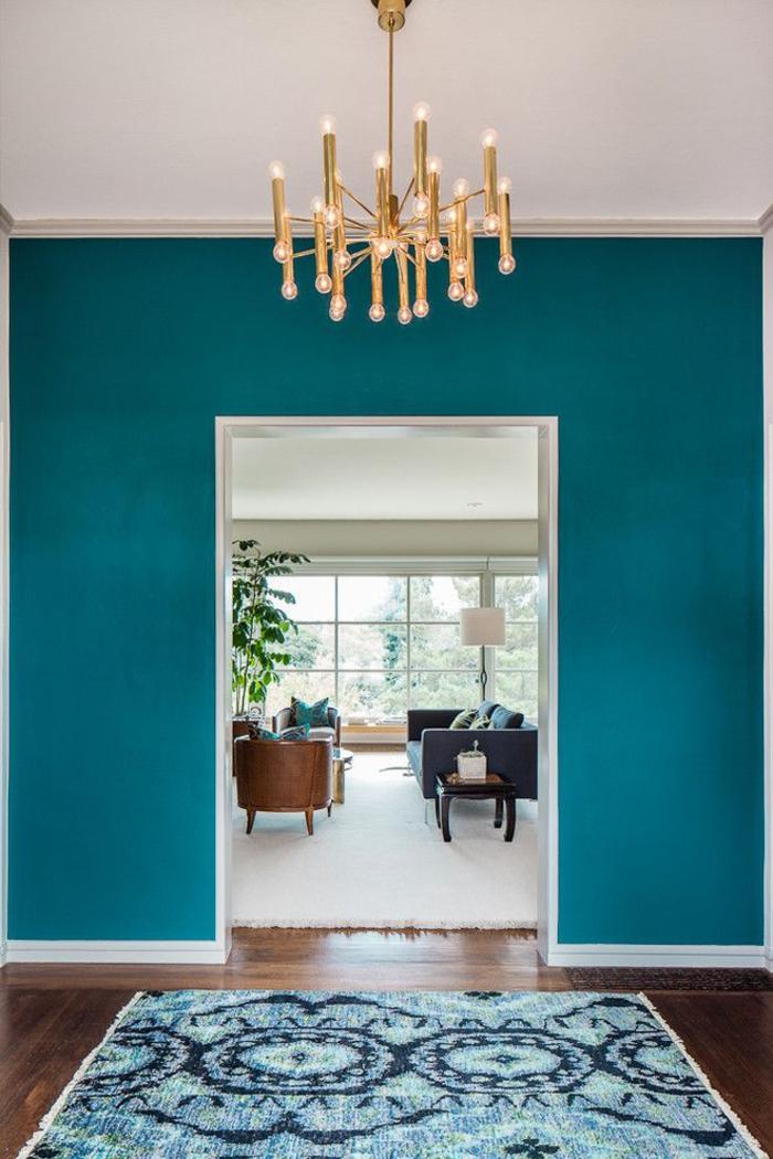 entrée en bleu paon pour une jolie ambiance tropicale, un lustre design sputnik en laiton pour une touche rétro chic