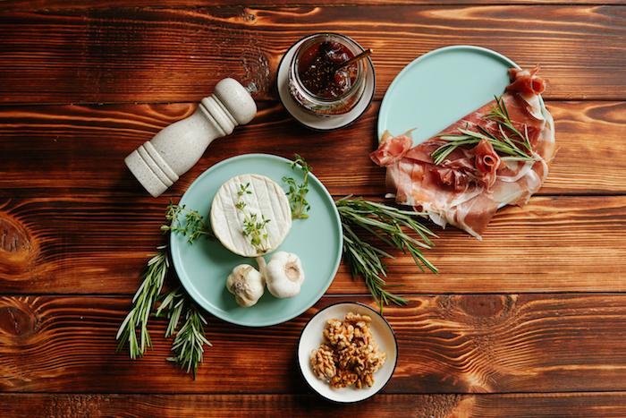 ingrédients nécessaires pour faire brie au four avec des tranches de prosciutto pour enrober le fromage de l ail des noix et du thym