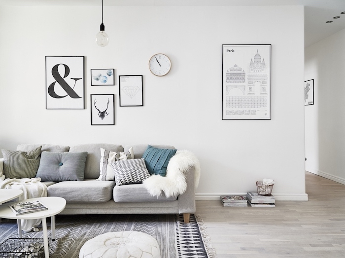 style scandinave, parquet de bois claire, art prints avec cadres noirs, pouf en cuir blanc, tapis en blanc et noir motifs géométriques
