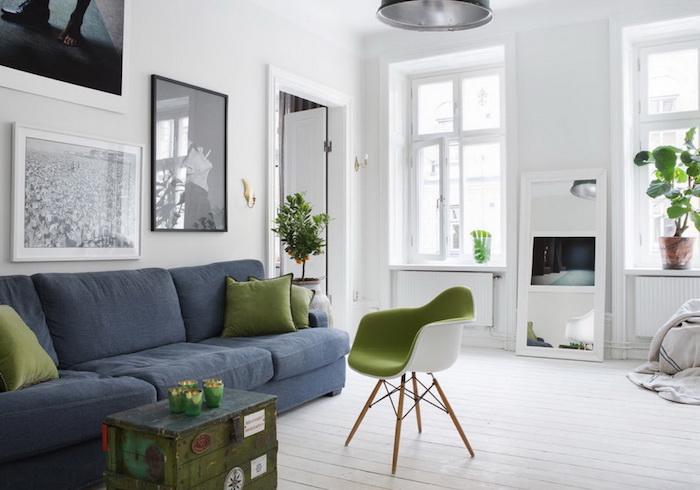 salon scandinave, parquet en bois peint en blanc, suspension luminaire métallique, canapé en tissu bleu foncé, coussin en vert