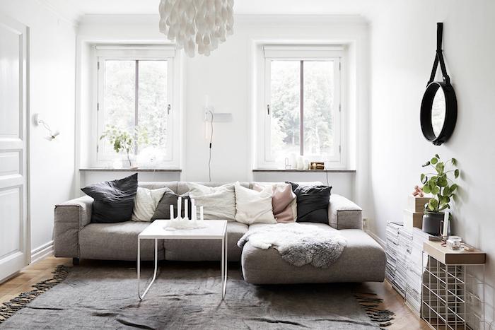 mobilier scandinave, parquet en bois clair, miroir rond en noir, murs peints en blanc, table en blanc, tapis gris avec franges
