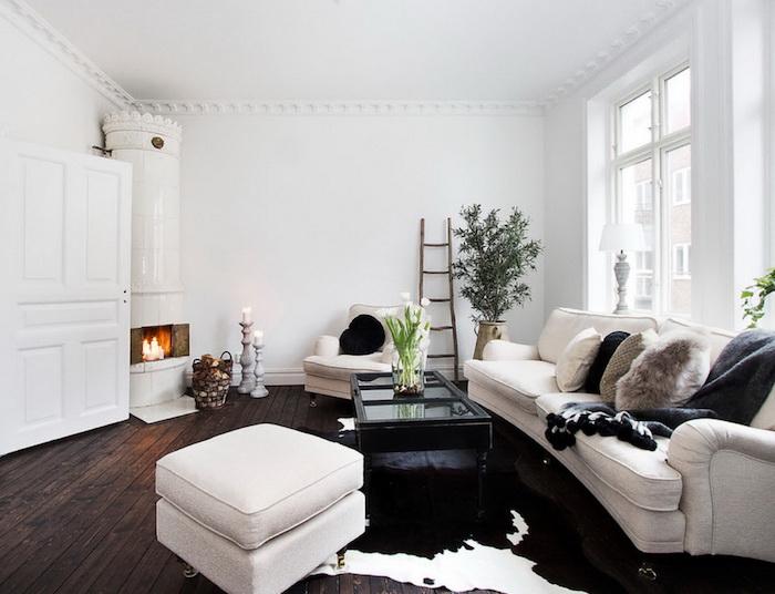 style scandinave, canapé blanc avec coussin en faux fur, cheminée blanche au coin, échelle décorative en bois