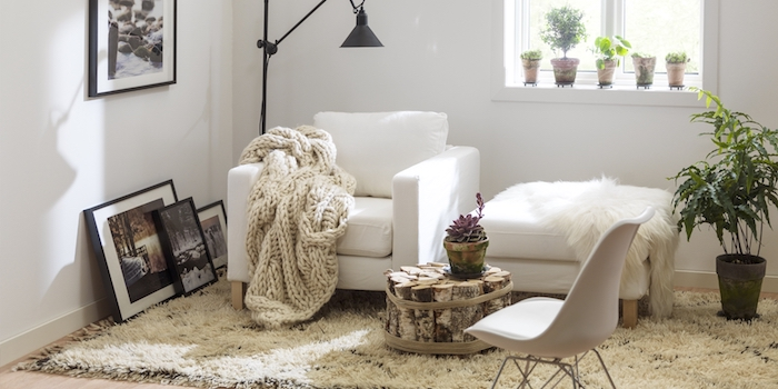 tapis scandinave, lampe sur pied en noir, plaid en crochet blanc, petite fleur verte, fauteuil en cuir blanc