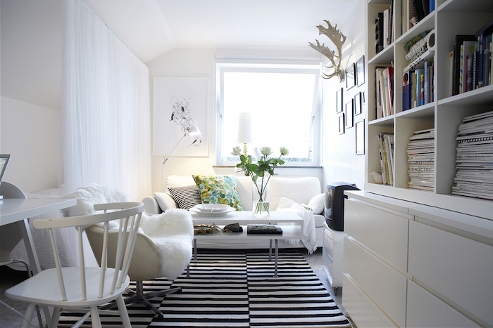 deco salon style scandinave, cornes de cerf en bois, rideaux longs en blanc, fauteuil blanc avec plaid en faux fur